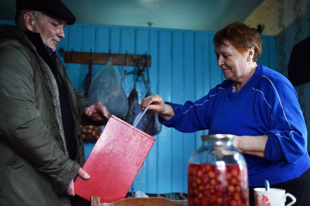 A woman casts her ballot as she votes at her home during Belarus' parliamentary election in the village of Rakautsy, some 95 km northwest of Minsk, on Sunday. — AFP