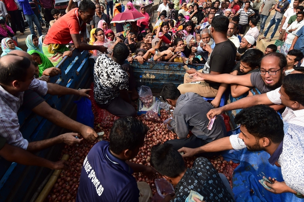 People scuffle as they purchase subsidized onions in Dhaka on Sunday. Bangladesh is urgently importing onions by air as the price of the essential ingredient in local cuisine soared to record highs, an official said. — AFP