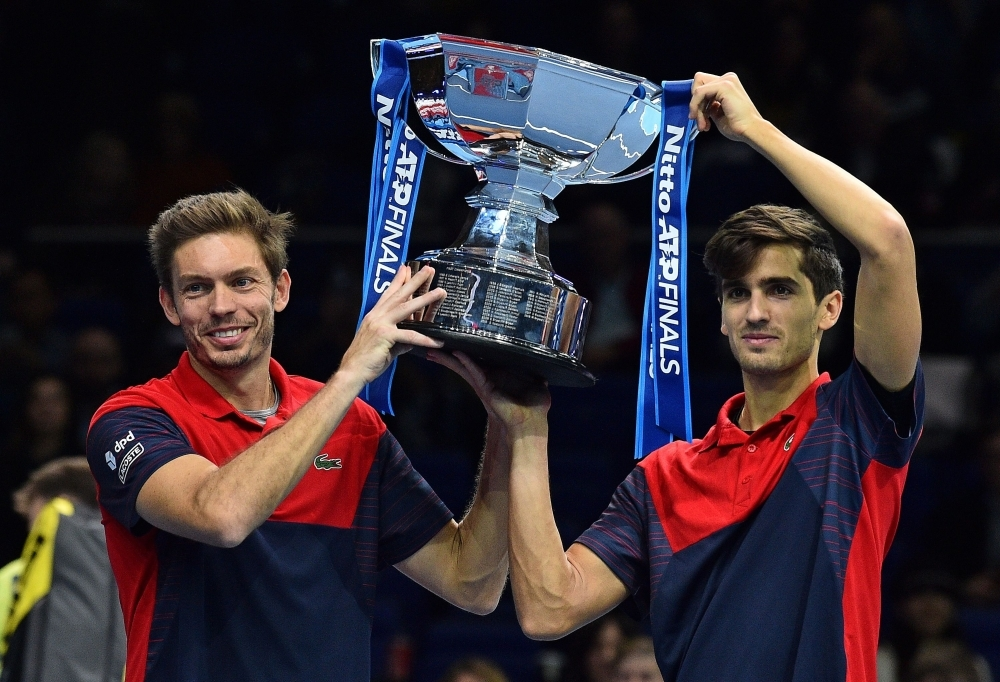 France's Nicolas Mahut (L) and France's Pierre-Hugues Herbert pose witht he winner's trophy after winning their men's doubles final match against returns against New Zealand's Michael Venus and South Africa's Raven Klaasen on day eight of the ATP World Tour Finals tennis tournament at the O2 Arena in London, on Sunday. Mahut and Herbet win the match 6-3, 6-4. — AFP