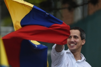 Venezuelan opposition leader and self-proclaimed acting president Juan Guaido displays a national flag during a gathering in front of the Bolivian embassy in Caracas on Saturday. -AFP