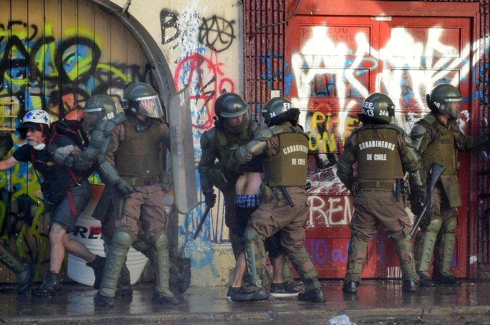 Riot policemen arrest demonstrators during a protest against the government in Santiago on Saturday. -AFP