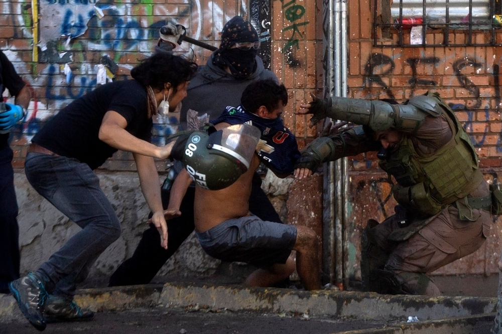 Demonstrators clash with riot police during a protest against the government in Santiago on Saturday. -AFP