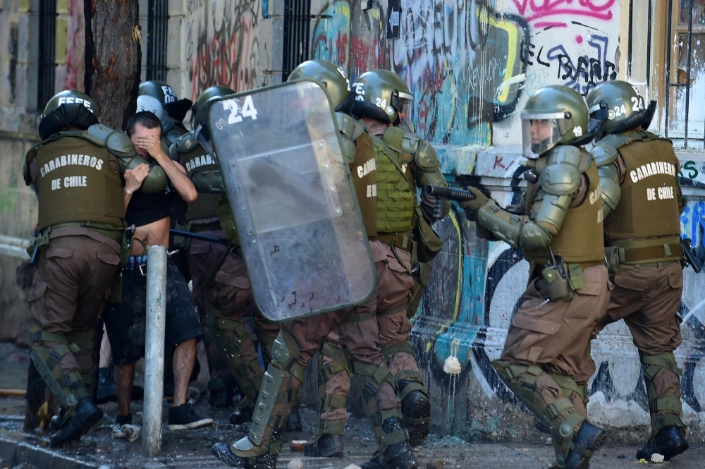 Riot policemen arrest a demonstrator during a protest against the government in Santiago on Saturday. -AFP
