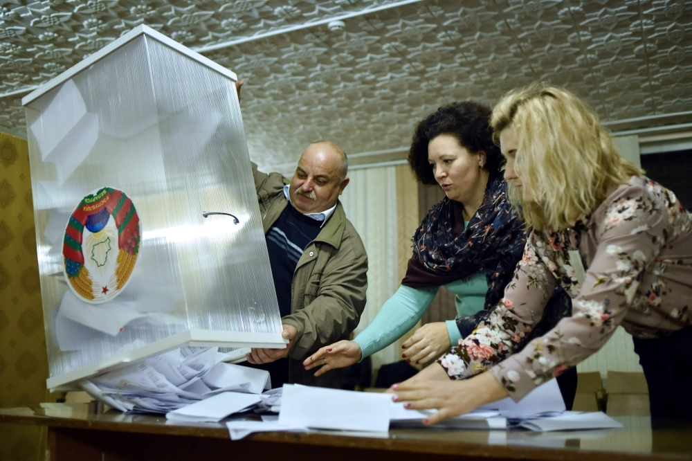 Members of a local electoral commission empty a ballot box to count votes at a polling station after the Belarus' parliamentary election in the village of Kreva, some 10 km northwest of Minsk, on Sunday. -AFP