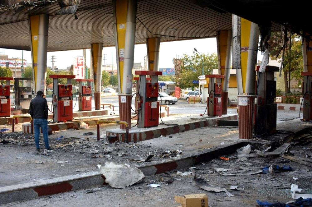 An Iranian man checks a scorched gas station that was set ablaze by protesters during a demonstration against a rise in gasoline prices in Eslamshahr, near the Iranian capital of Tehran, on Sunday. — AFP