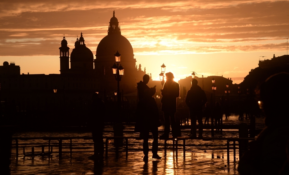 Visitors walk at the sunset in the flooded street in Venice, during