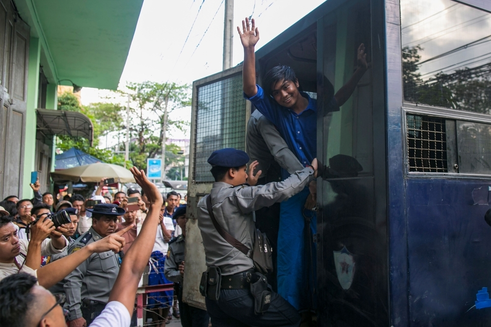 Zayer Lwin, a performer of Peacock Generation group, waves from a prison van after a trial in Yangon on Monday. — AFP