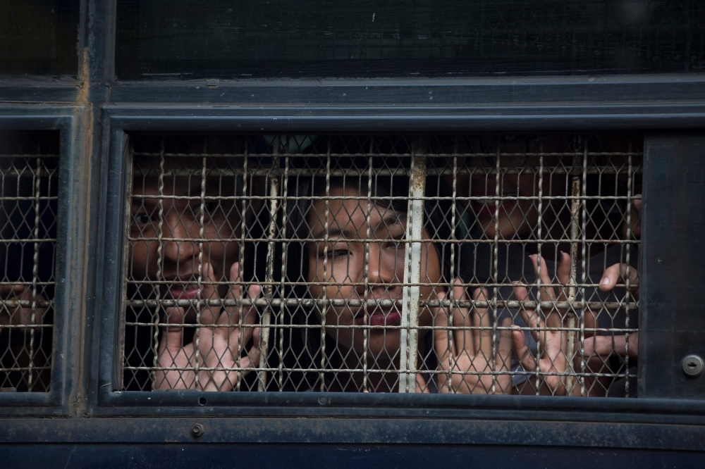 Kay Khaing Tun, a performer of Peacock Generation group, looks from a prison van window after a trial in Yangon on Monday. — AFP