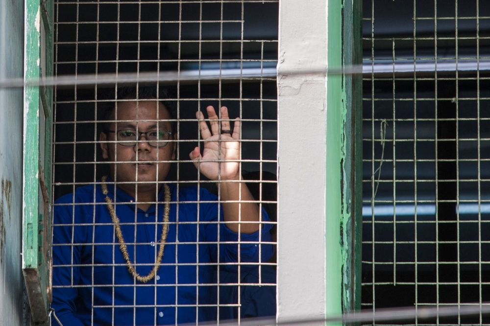 Paing Ye Thu, a performer of Peacock Generation group, looks from a court window during a trial in Yangon on Monday. — AFP