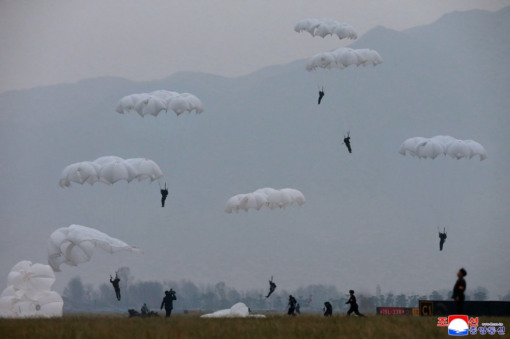 Members of the Air and Anti-Aircraft Force of the Korean People's Army are seen parachuting during airborne insertion training at an undisclosed location. — AFP