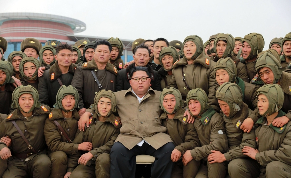 North Korean leader Kim Jong Un poses with members of the Air and Anti-Aircraft Force of the Korean People's Army during an airborne insertion training at an undisclosed location. — AFP