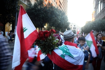 A street vendor sells roses and Lebanese flags to anti-government protesters during a demonstration in downtown Beirut on Sunday. -AFP
