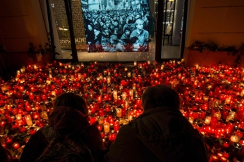 People place candles at a memorial to commemorate the 30th anniversary of the so-called Velvet Revolution on Sunday in Prague. -AFP