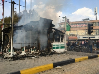 Iranians gather around a charred police station that was set ablaze by protesters during a demonstration against a rise in gasoline prices in the central city of Isfahan on Sunday. -AFP