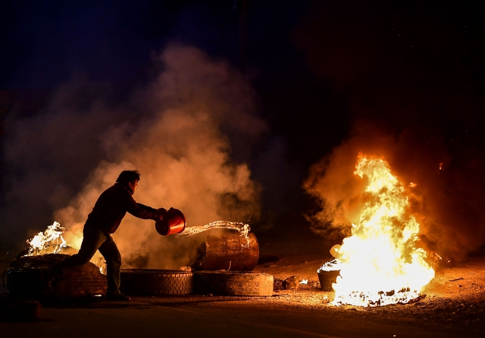 A man extinguishes the fire of a blockade set by supporters of Bolivian ex-President Evo Morales in the outskirts of Sacaba, Chapare province, Cochabamba, on Monday. -AFP