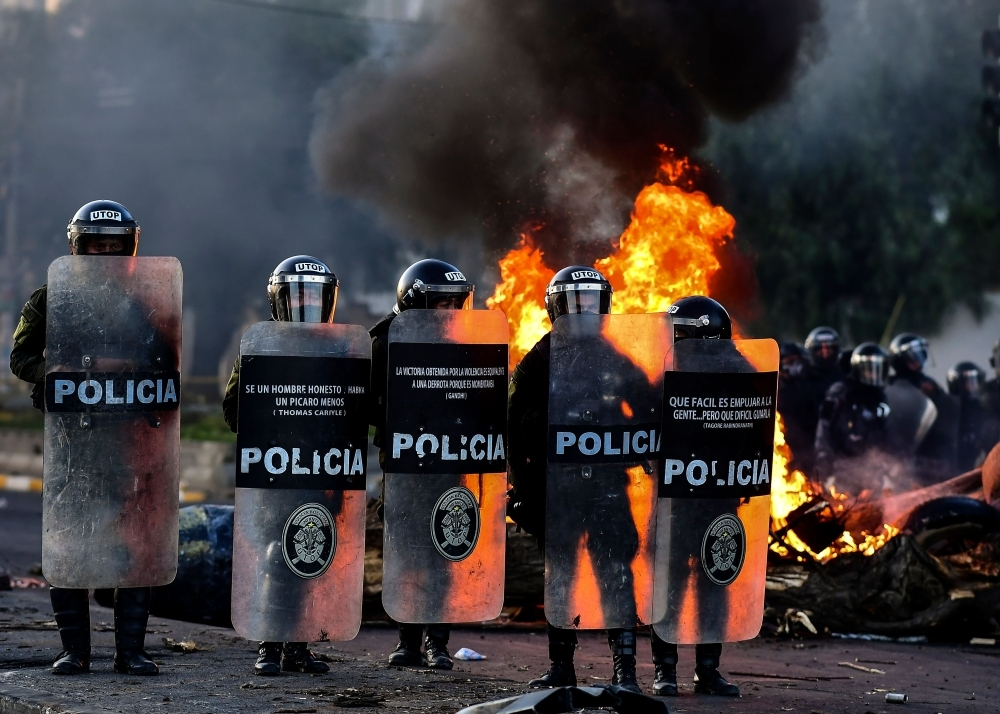 Bolivian riot police take position as supporters of Bolivian ex-President Evo Morales block a road in the outskirts of Sacaba, Chapare province, Cochabamba, on Monday. -AFP
