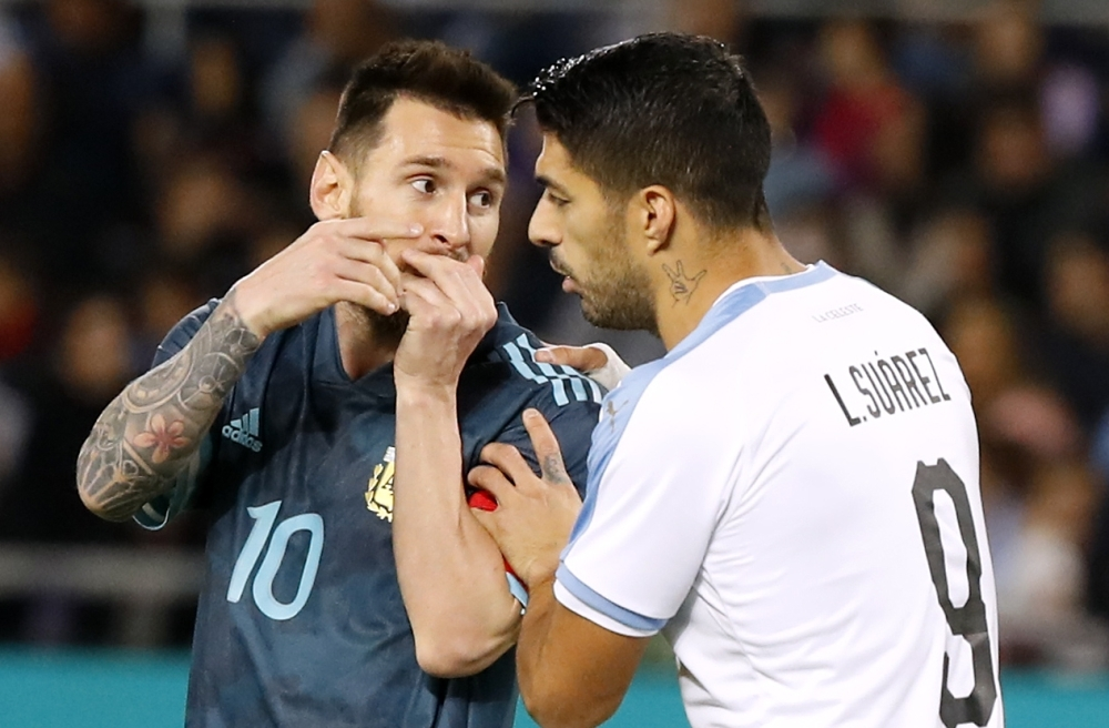Argentina's forward Lionel Messi talks with Uruguay's forward Luis Suarez during the friendly football match between Argentina and Uruguay at the Bloomfield stadium in the Israeli coastal city of Tel Aviv on Monday. — AFP