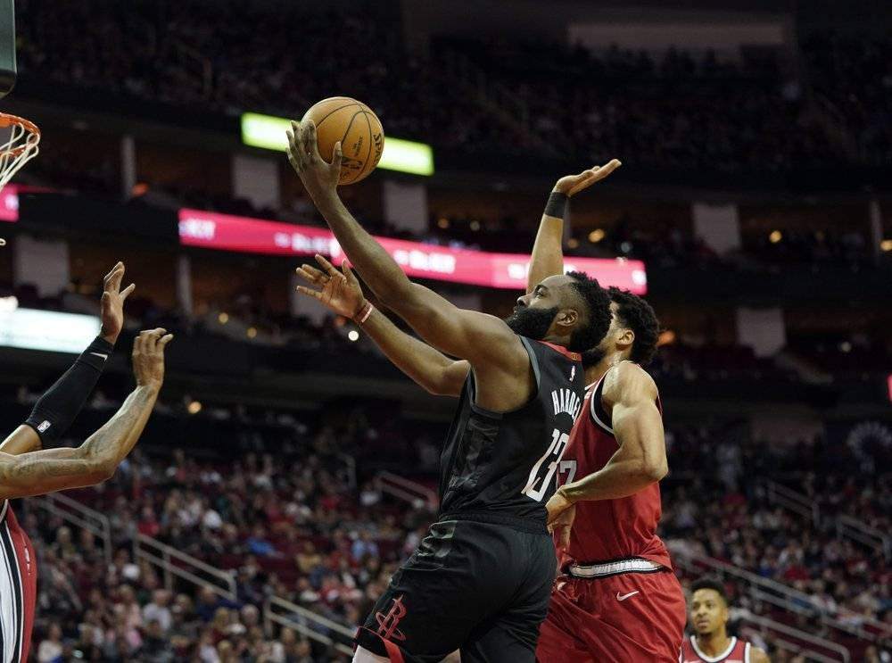 Houston Rockets' James Harden (13) goes up for a shot as Portland Trail Blazers' Skal Labissiere, right, defends during the first half of an NBA basketball game in Houston on Monday. — AFP