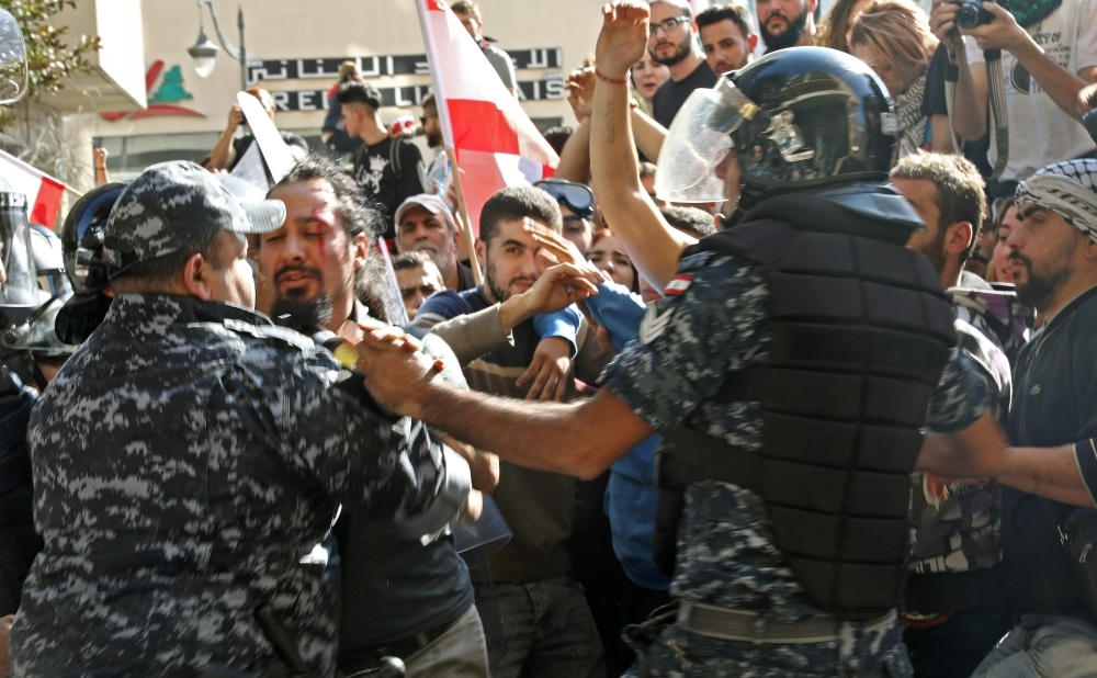 Lebanese protesters scuffle with security forces near the parliament headquarters in the capital Beirut's downtown district on Tuesday. — AFP