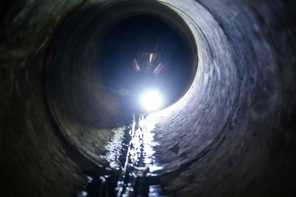 A protester uses a torch light while crawling within a sewer tunnel to see how wide it is as he and others try to find an escape route from the Hong Kong Polytechnic University in the Hung Hom district of Hong Kong early morning on Tuesday. — AFP