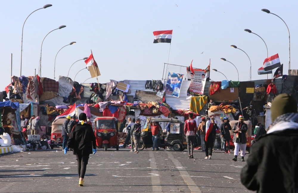 Iraqi anti-government protesters gather at a sit-in near barricades over Al-Sinek bridge connecting the Iraqi capital Baghdad's Sinek district to the Salhiyeh district neighboring the high-security Green Zone, which hosts government offices and foreign embassies, on Tuesday. — AFP