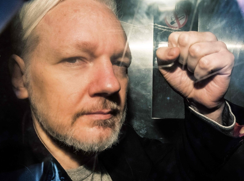 WikiLeaks founder Julian Assange gestures from the window of a prison van as he is driven into Southwark Crown Court in London in this May 1, 2019 file photo. — AFP