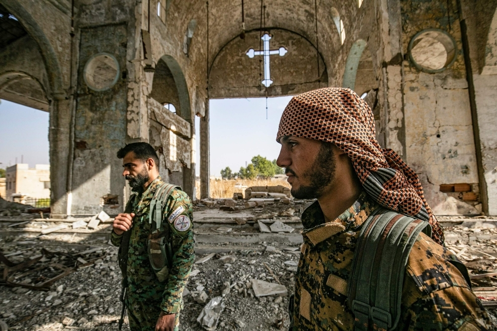 Members of the Khabour Guards (MNK) Assyrian Syrian militia, affiliated with the Syrian Democratic Forces (SDF), walk in the ruins of the Assyrian Church of the Virgin Mary, which was previously destroyed by Daesh (the so-called IS) fighters, in the village of Tal Nasri south of the town of Tal Tamr in Syria's northeastern Hasakah province in this Nov. 15, 2019 file photo. — AFP