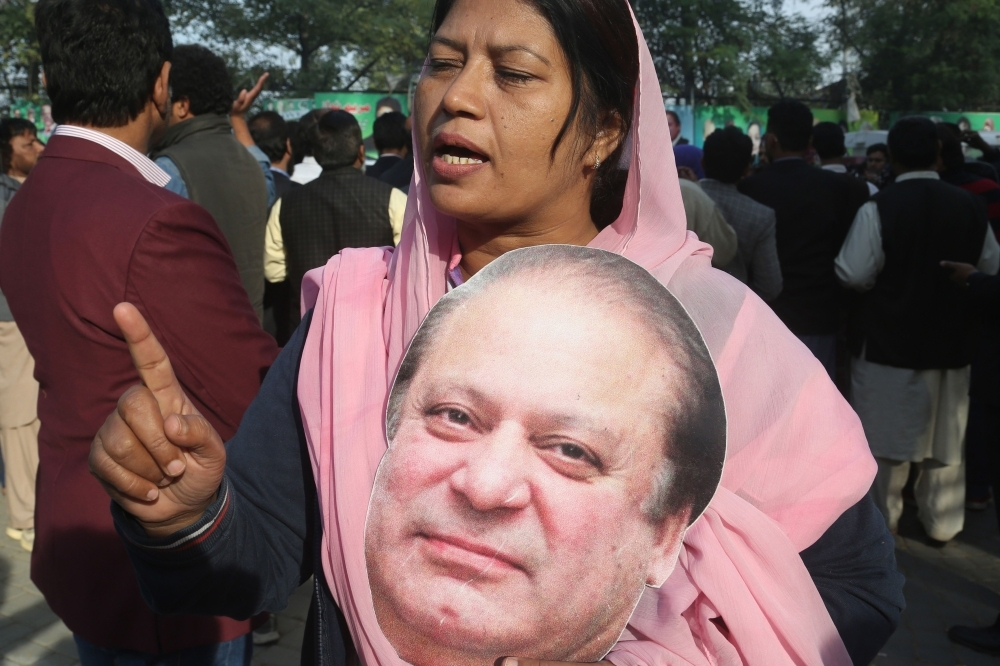 A supporter of Pakistan Muslim League Nawaz (PML-N) holds a cut out picture of the ailing former Pakistani Prime Minister Nawaz Sharif outside his residence before he traveled to Lahore airport prior to his departure for abroad for medical treatment, in Lahore, Pakistan, on Tuesday. — AFP
