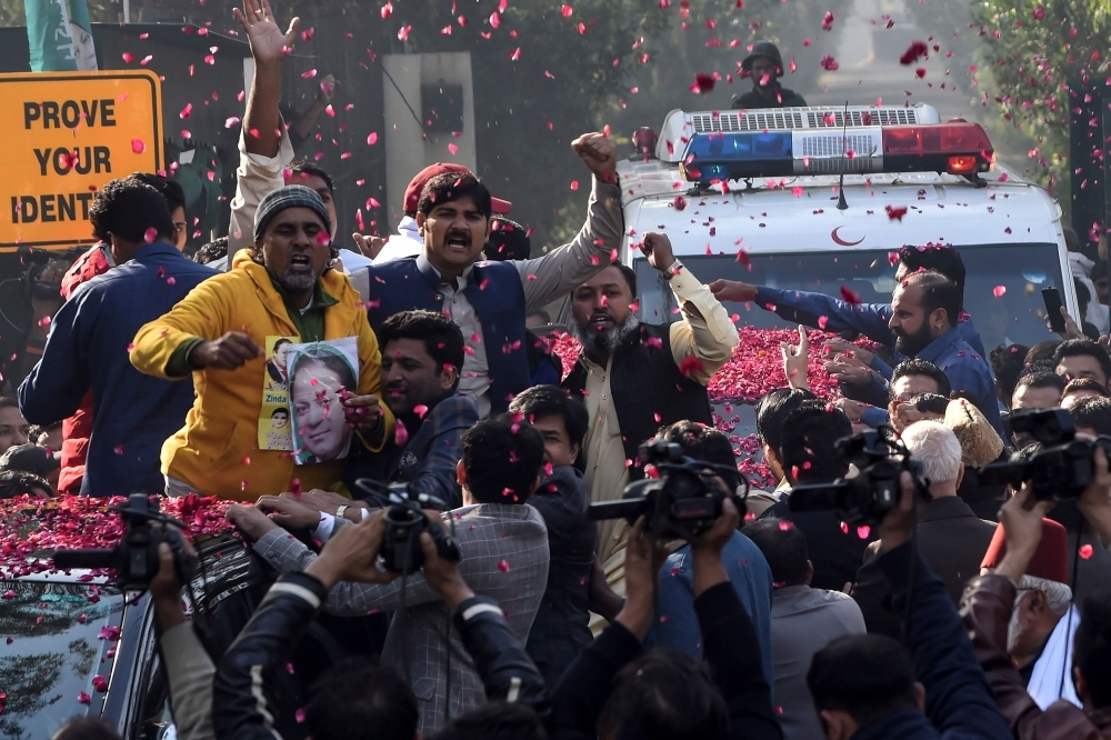 Supporters of Pakistan Muslim League Nawaz (PML-N) gather around a vehicle, covered with rose petals, carrying the ailing former Pakistani Prime Minister Nawaz Sharif outside his residence before he traveled to Lahore airport prior to his departure for abroad for medical treatment, in Lahore, Pakistan, on Tuesday. — AFP