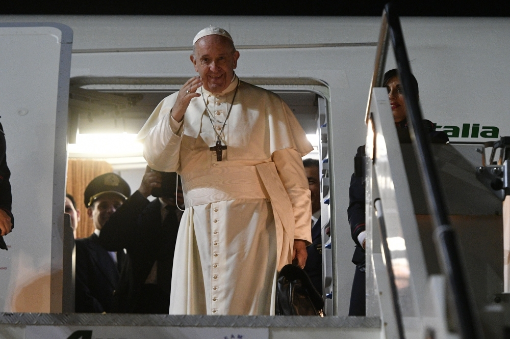 Pope Francis waves as he boards his plane to depart for a one-week trip to Thailand and Japan at Rome's Fiumicino airport on Tuesday. — AFP