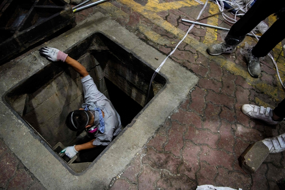 A protester climbs down into a sewer entrance with a guide string, center, as he and others try to find an escape route from the Hong Kong Polytechnic University in the Hung Hom district of Hong Kong, early morning on Tuesday. — AFP