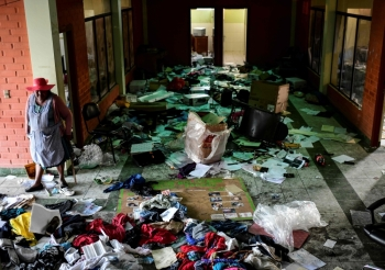 A woman stands looking inside a police station after it was looted, in Sacaba, Chapare province, Cochabamba, on Tuesday. -AFP