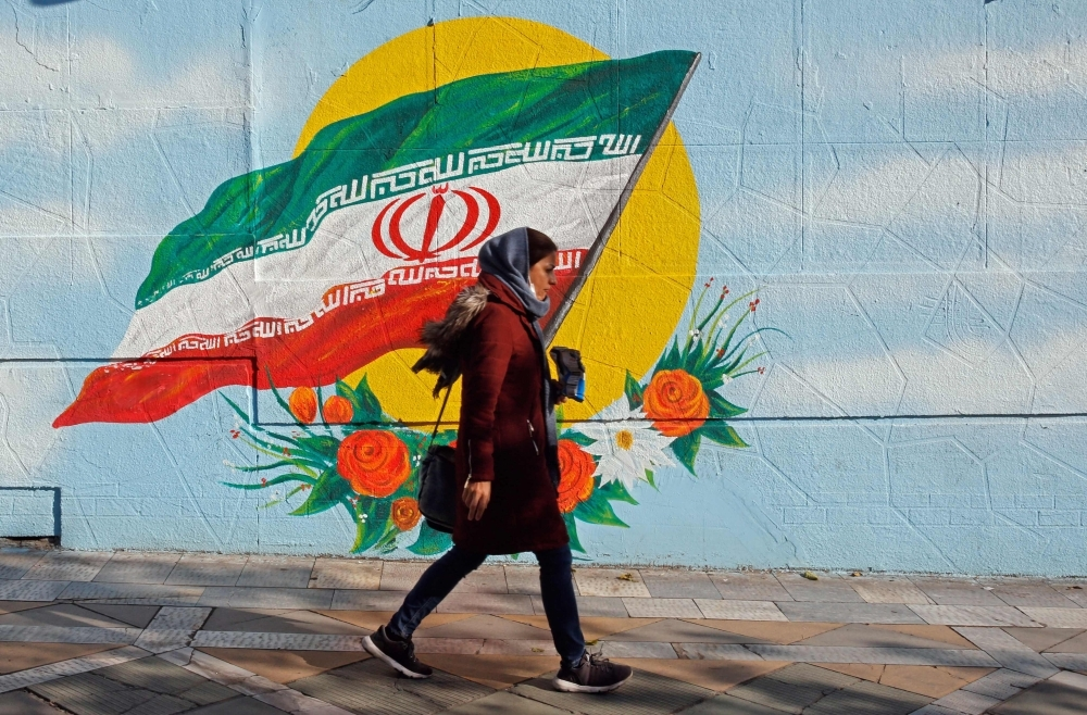 An Iranian woman walks past a mural painting of the Islamic republic's national flag in central Tehran on Thursday. — aFP