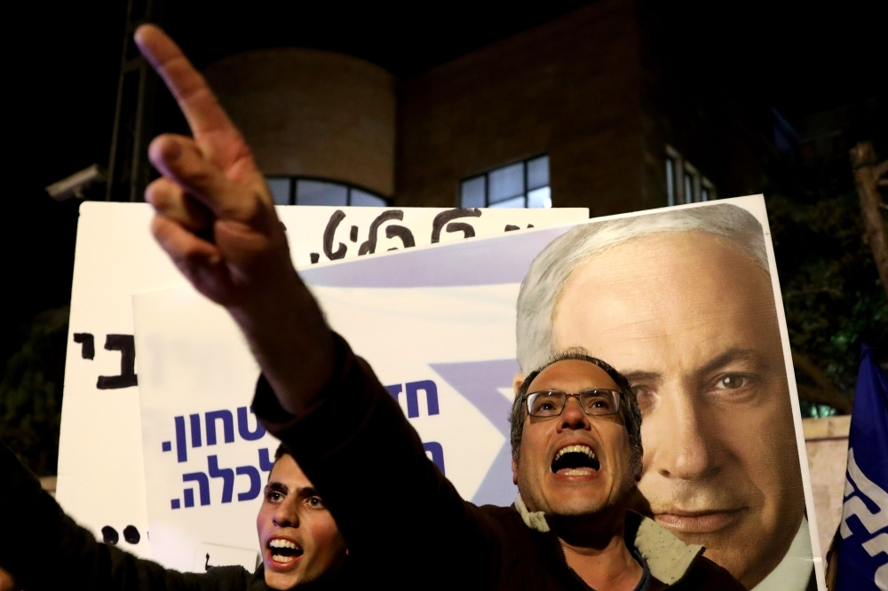 Supporters of Israeli Prime Minister Benjamin Netanyahu chant slogans as they demonstrate their solidarity with him outside his official residency in Jerusalem on Thursday. Sign in Hebrew reads: