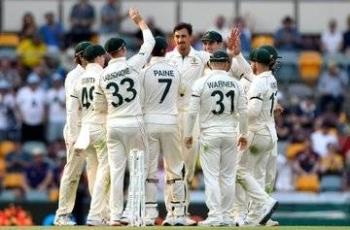 Australia team celebrates with Michael Starc, who helped his team seize the advantage on the opening day of the first Test against Pakistan at the Gabba in Brisbane on Thursday.