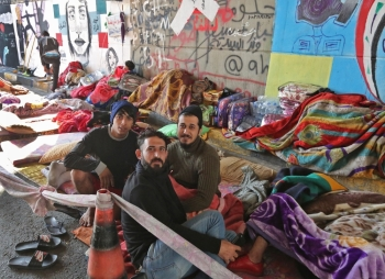 Iraqi anti-government protesters are pictured where they sleep on the side of a road surrounded by graffiti the Iraqi capital Baghdad's Tahrir square on Wednesday. — AFP