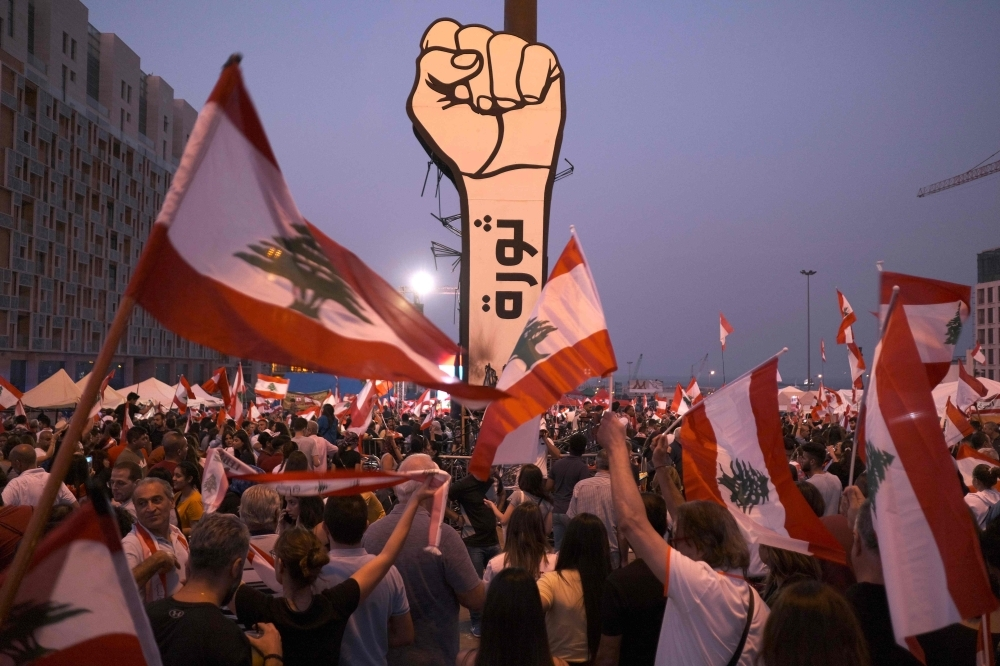 Protesters wave Lebanese national flags by a giant sign of a fist with the slogan