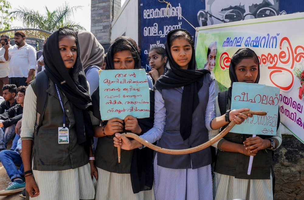 Students hold placards and a toy snake during a protest over the death of a girl after she was bitten by a snake inside her classroom at Sulthan Bathery in Wayanad's district in Indian southern state of Kerala on Friday. — AFP