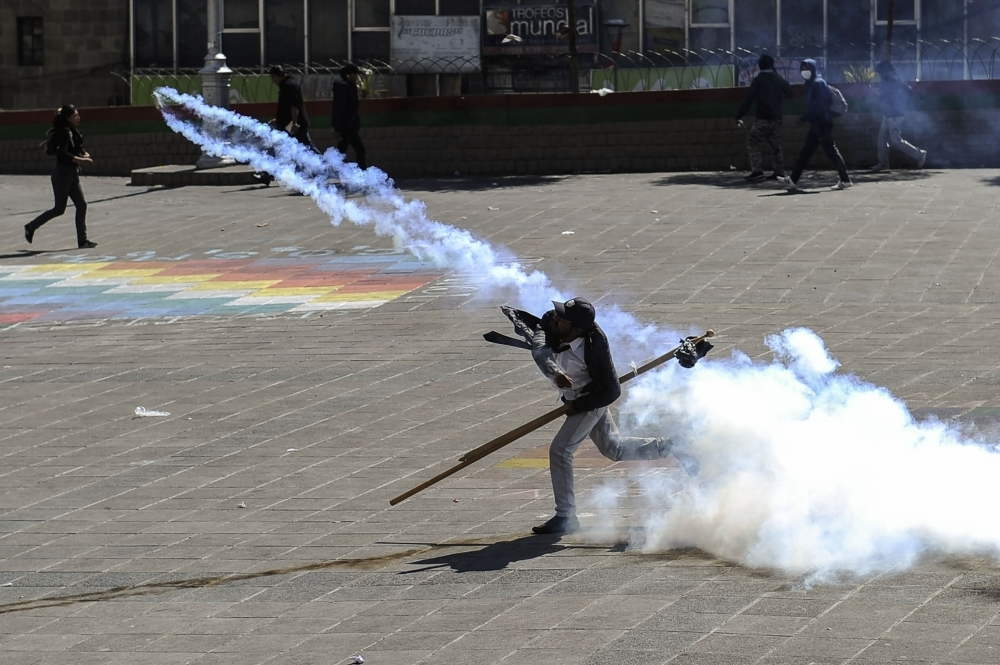 A man attending the funeral procession of eight supporters of Bolivia's ex-President Evo Morales, killed when security forces lifted a siege on a fuel plant, throws a tear gas canister back at riot police, in La Paz on Thursday. — AFP