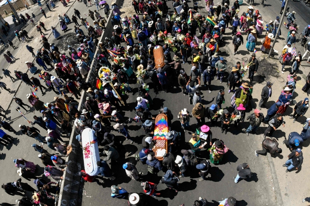 Men carry the coffins of three of eight supporters of Bolivia's ex-President Evo Morales, killed when security forces lifted a siege on a fuel plant, during a funeral procession in El Alto, Bolivia, on on Thursday. — AFP