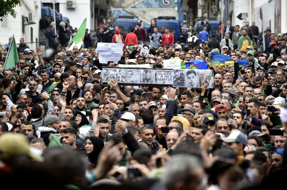 Algerian protesters lift banners as they take part in an anti-government demonstration in the center of the capital Algiers on Friday. — AFP