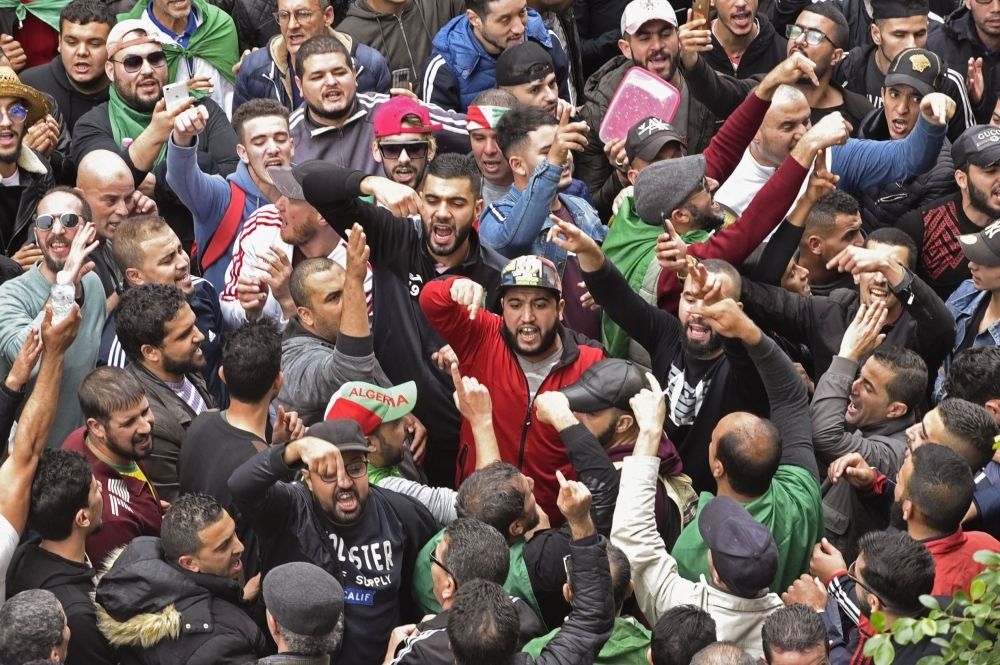 Algerian protesters gesture as they chant during an anti-government demonstration in the center of the capital Algiers on Friday. — AFP
