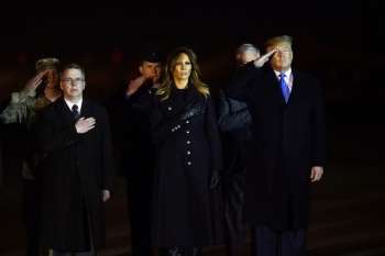 US President Donald J. Trump, first lady Melania Trump and US Deputy Secretary of Defense David Norquist (L) salute as military personnel carry a transfer case for fallen service member, US Army Chief Warrant Officer 2 Kirk T. Fuchigami, 25, during a dignified transfer at Dover Air Force Base on Thursday in Dover, Delaware. — AFP