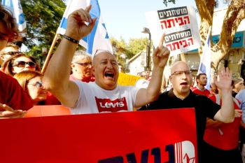 Supporters of Israel's Labour party chant slogans and hold flags and banners as they attend a rally against Israeli Prime Minister Benjamin Netanyahu outside the Likud party headquaters in the coastal Mediterranean city of Tel Aviv on Friday. — AFP