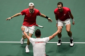 Canada's Vasek Pospisil (R) and Denis Shapovalov celebrate with Canada's captain Frank Dancevic (C) after winning a quarterfinal doubles tennis match against Australia at the Davis Cup Madrid Finals 2019 in Madrid on Thursday. — AFP