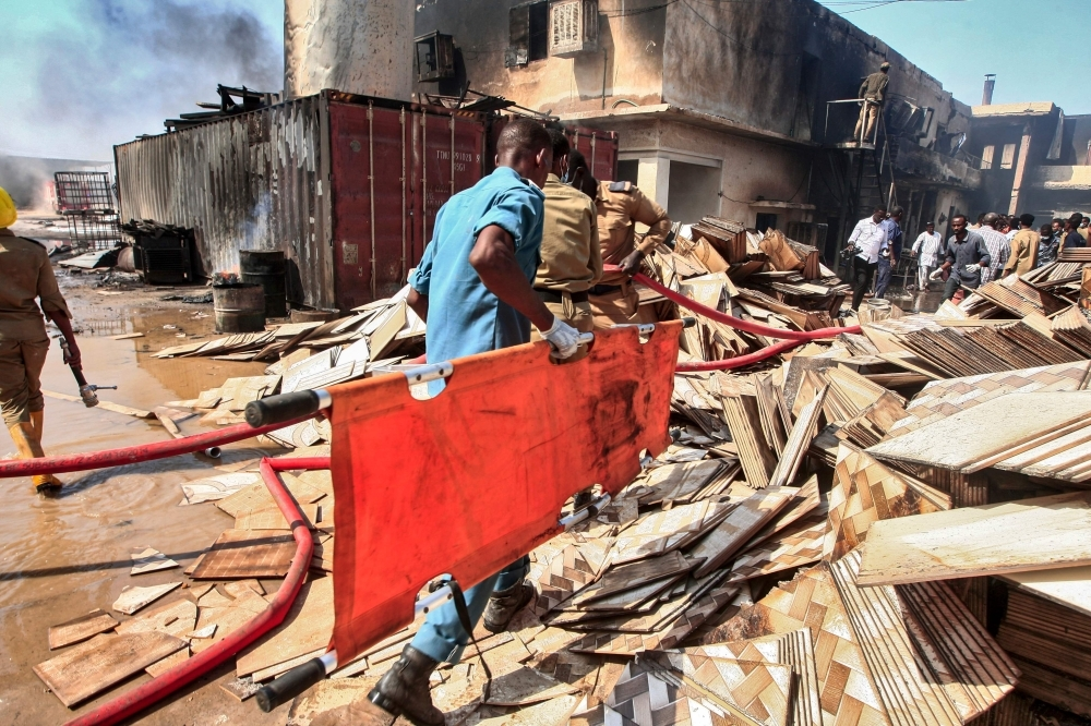 A Sudanese paramedic walks with a stretcher as others search for victims at the scene of a fire at a tile manufacturing unit in an industrial zone in north Khartoum on Tuesday. — AFP
