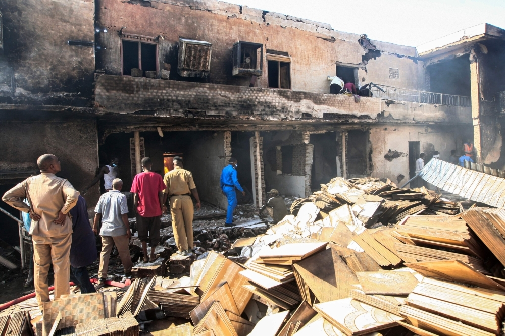Members of the Sudanese Civil Defense search for victims at the scene of a fire at a tile manufacturing unit in an industrial zone in north Khartoum on Tuesday. — AFP