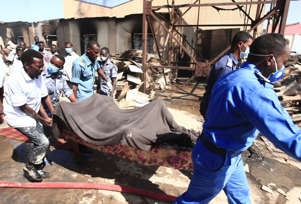 Members of the Sudanese Civil Defense transport the bodies of victims of a fire at a tile manufacturing unit in an industrial zone in north Khartoumon Tuesday. — AFP