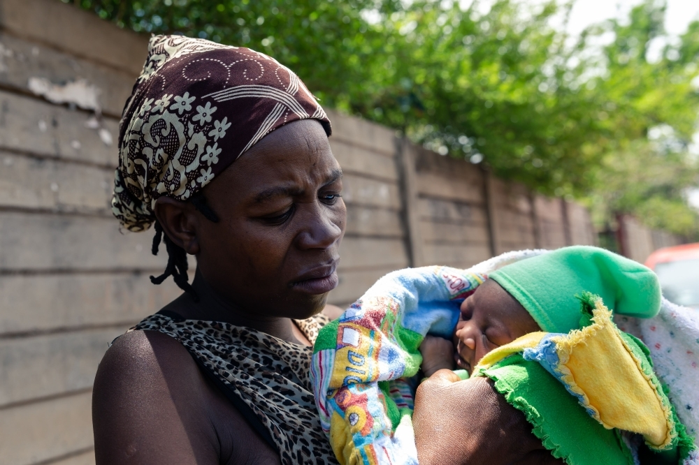 Winnie Denhere cradling her two-day-old baby boy delivered by Esther Gwena outside  Edith Opperman clinic where the baby is to receive a BCG vaccine injection in Mbare high-density suburb in Harare, on November 21, 2019. -AFP