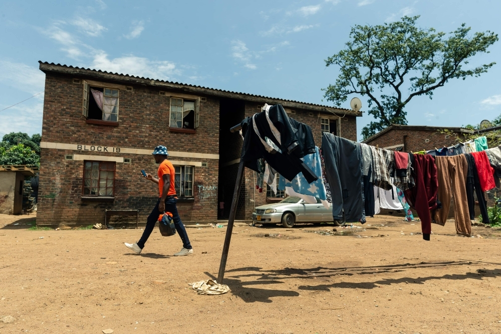 A man walks past the first floor apartment of sixty-nine-year-old Esther Gwena's two-room apartment in Mbare high-density suburb in Harare, on November 21, 2019. -AFP